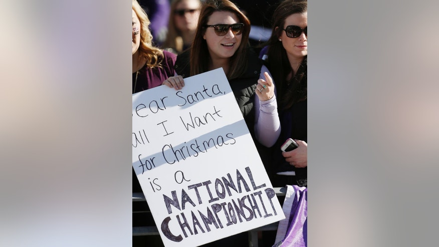 A TCU fan holds up a sign showing her desire for a National Championship during the first half of an NCAA college football game against Iowa State at Amon G. Carter Stadium, Saturday, Dec. 6, 2014, in Fort Worth, Texas. TCU won 55-3. (AP Photo/Brandon Wade)
