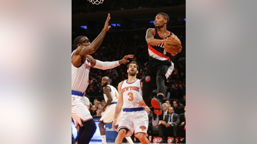 Portland Trail Blazers' Damian Lillard (0) looks to pass away from New York Knicks' Jose Calderon (3) and Amar'e Stoudemire during the first half of an NBA basketball game Sunday, Dec. 7, 2014, in New York.  (AP Photo/Frank Franklin II)