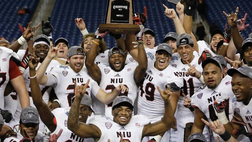 The Northern Illinois Huskies raise the trophy after winning their Mid-American Conference championship NCAA college football game against Bowling Green 51-17 in Detroit, Friday, Dec. 5, 2014. (AP Photo/Carlos Osorio)