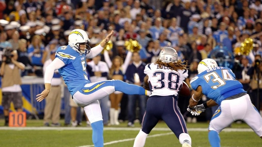 San Diego Chargers punter Mike Scifres is hit as he punts by New England Patriots'  Brandon Bolden during the first half in an NFL football game Sunday, Dec. 7, 2014, in San Diego. (AP Photo/Lenny Ignelzi)