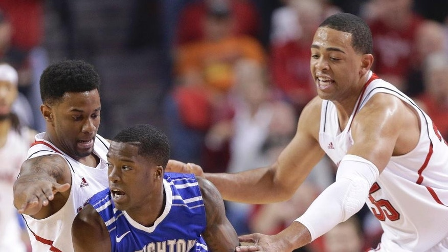 Creighton's Austin Chatman (1) is defended by Nebraska's Benny Parker, left, and Nebraska's Walter Pitchford (35) during the first half of an NCAA college basketball game in Lincoln, Neb., Sunday, Dec. 7, 2014. (AP Photo/Nati Harnik)