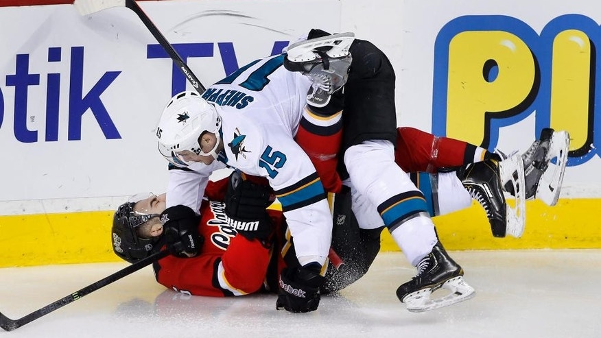 Calgary Flames' Mark Giordano, bottom, is pushed down by San Jose Sharks' James Sheppard during the first period of an NHL hockey game in Calgary, Alberta, Saturday Dec. 6, 2014. (AP Photo/The Canadian Press, Larry MacDougal)