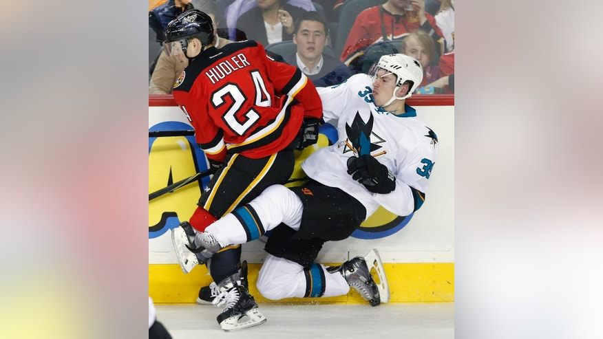 San Jose Sharks' Logan Couture, right, is knocked down by Calgary Flames' Jiri Hudler, from Czech Republic, during the first period of an NHL hockey game in Calgary, Alberta, Saturday, Dec. 6, 2014. (AP Photo/The Canadian Press, Larry MacDougal)