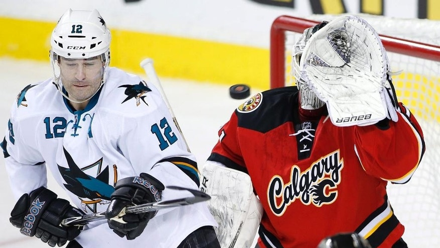Calgary Flames goalie Karri Ramo, right, from Finland, makes a save despite being screened by San Jose Sharks' Patrick Marleau during the second period of an NHL hockey game in Calgary, Alberta, Saturday, Dec. 6, 2014. (AP Photo/The Canadian Press, Larry MacDougal)