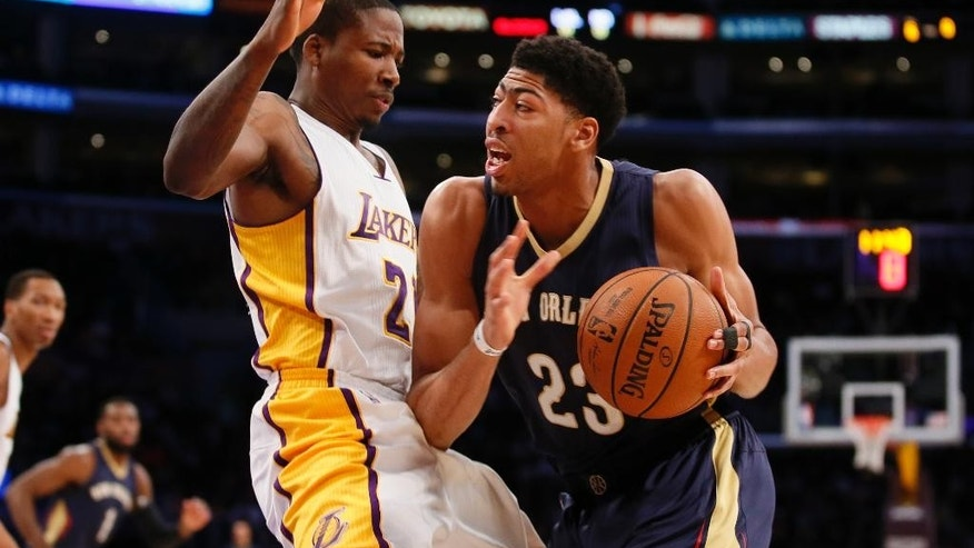 New Orleans Pelicans' Anthony Davis, right, drives against Los Angeles Lakers' Wayne Ellington, left, during the first half of an NBA basketball game Sunday, Dec. 7, 2014, in Los Angeles. (AP Photo/Danny Moloshok)