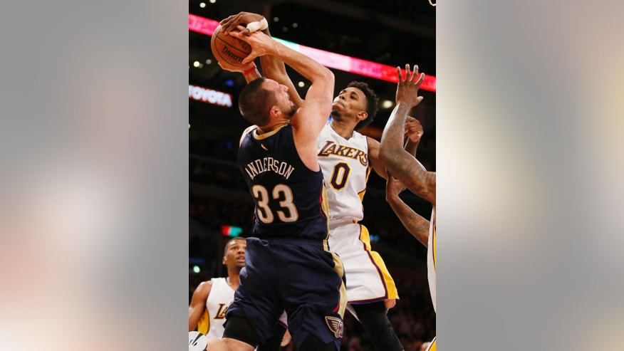 Los Angeles Lakers' Nick Young, right, blocks a shot by New Orleans Pelicans' Ryan Anderson, left, during the first half of an NBA basketball game Sunday, Dec. 7, 2014, in Los Angeles. (AP Photo/Danny Moloshok)