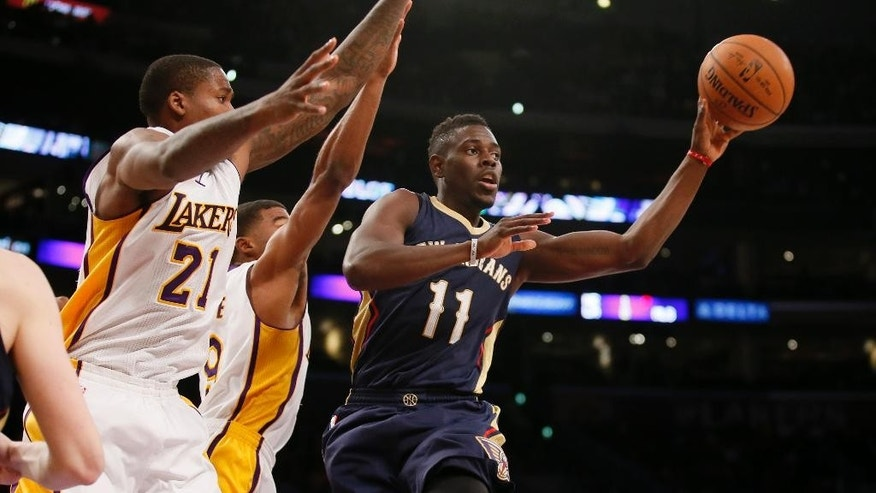 New Orleans Pelicans' Jrue Holiday, right, passes the ball off as Los Angeles Lakers' Ed Davis, left, and Ronnie Price, rear, defend him during the first half of an NBA basketball game Sunday, Dec. 7, 2014, in Los Angeles. (AP Photo/Danny Moloshok)