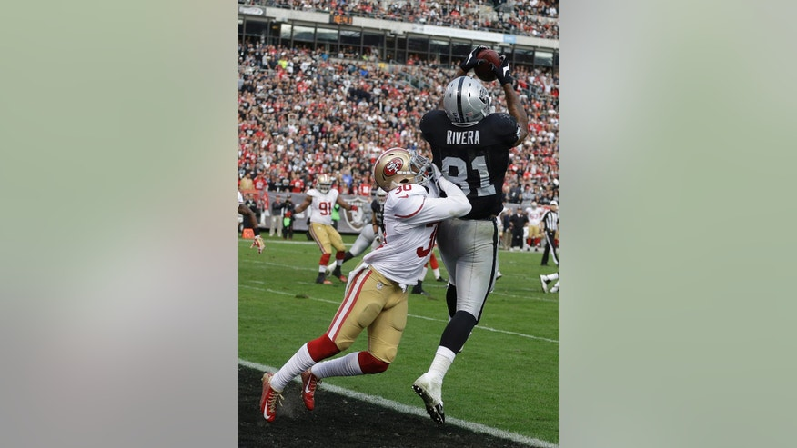 Oakland Raiders tight end Mychal Rivera (81) catches a 5-yard touchdown pass in front of San Francisco 49ers defensive back Leon McFadden (30) during the fourth quarter of an NFL football game in Oakland, Calif., Sunday, Dec. 7, 2014. (AP Photo/Ben Margot)
