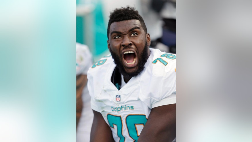 Miami Dolphins defensive end Terrence Fede reacts from the bench after watching a play during the second half of an NFL football game against the Baltimore Ravens, Sunday, Dec. 7, 2014 in Miami Gardens, Fla. The Ravens defeated the Dolphins 28-13. (AP Photo/Wilfredo Lee)