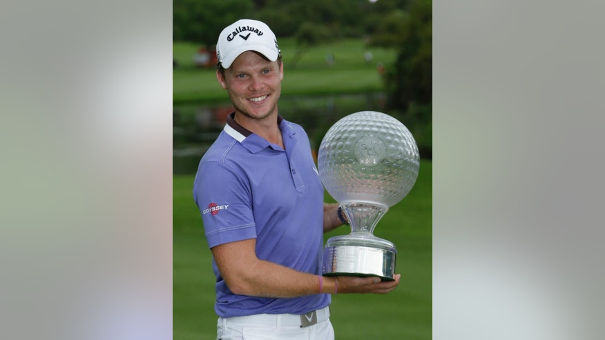 Danny Willett of England holds the trophy after winning the Nedbank Golf Challenge at the Gary Player Country Club in Sun City, South Africa on Sunday Dec. 7, 2014. (AP Photo/Themba Hadebe)