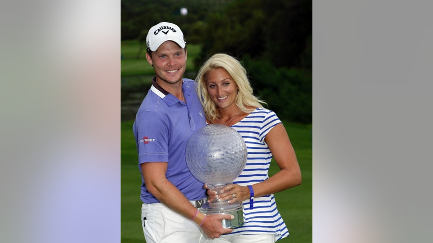 Danny Willett of England, left, poses with his wife Nicole, right, with the trophy after winning the the Nedbank Golf Challenge, at the Gary Player Country Club in Sun City, South Africa, Sunday Dec. 7, 2014. (AP Photo/Themba Hadebe)