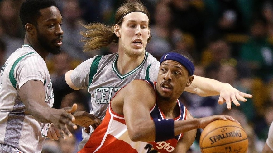 Washington Wizards forward Paul Pierce, right, looks for an opening around Boston Celtics forward Jeff Green, left, and center Kelly Olynyk, behind, in the second quarter of an NBA basketball game, Sunday, Dec. 7, 2014, in Boston. (AP Photo/Steven Senne)