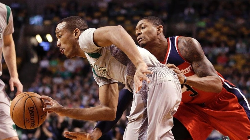 Boston Celtics guard Avery Bradley, left, drives toward the basket as Washington Wizards guard Bradley Beal, right, follows in the first quarter of an NBA basketball game, Sunday, Dec. 7, 2014, in Boston. (AP Photo/Steven Senne)