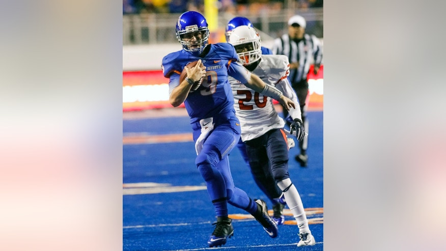 Boise State quarterback Grant Hedrick (9) runs the ball past Fresno State defensive back Malcolm Washington (20) during the first half of the Mountain West Conference championship NCAA college football game in Boise, Idaho, on Saturday, Dec. 6, 2014. (AP Photo/Otto Kitsinger)