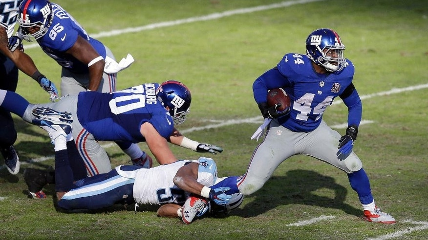 New York Giants running back Andre Williams (44) runs out of the grasp of Tennessee Titans linebacker Wesley Woodyard (59) in the second half of an NFL football game Sunday, Dec. 7, 2014, in Nashville, Tenn. (AP Photo/James Kenney)