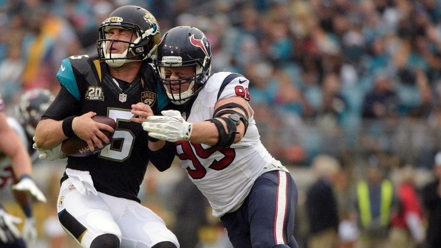 Jacksonville Jaguars quarterback Blake Bortles (5) is sacked by Houston Texans defensive end J.J. Watt (99) during the first half of an NFL football game in Jacksonville, Fla., Sunday, Dec. 7, 2014. (AP Photo/Phelan M. Ebenhack)