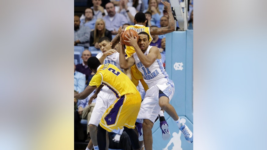 North Carolina's Brice Johnson (11) grabs a rebound against East Carolina's Caleb White (2) and Terry Whisnant, rear, as North Carolina's Justin Jackson reaches at left during the second half of an NCAA college basketball game in Chapel Hill, N.C., Sunday, Dec. 7, 2014. North Carolina won 108-64. (AP Photo/Gerry Broome)