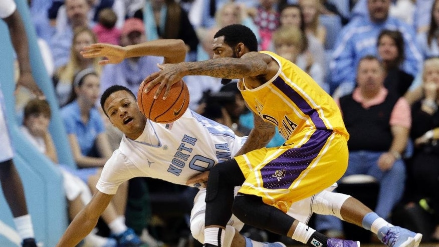 North Carolina's Nate Britt (0) guards East Carolina's Terry Whisnant during the second half of an NCAA college basketball game in Chapel Hill, N.C., Sunday, Dec. 7, 2014. North Carolina won 108-64. (AP Photo/Gerry Broome)