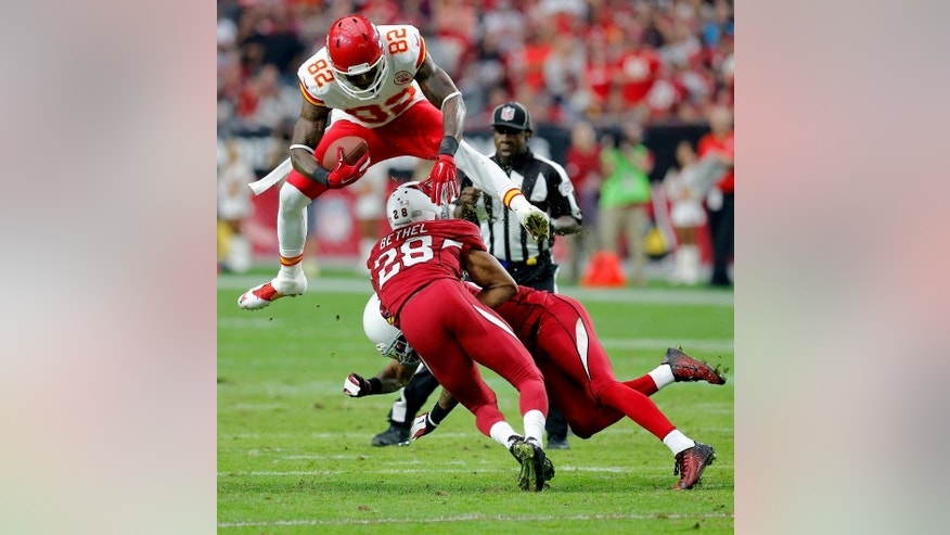 Kansas City Chiefs wide receiver Dwayne Bowe (82) leaps over Arizona Cardinals cornerback Justin Bethel (28) and Rashad Johnson during the first half of an NFL football game, Sunday, Dec. 7, 2014, in Glendale, Ariz. (AP Photo/Rick Scuteri)