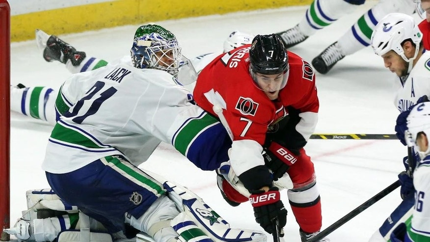 Vancouver Canucks goalie Eddie Lack (30 ) and Ottawa Senators' Kyle Turris (7) battle for the puck during an NHL hockey game in Ottawa, Ontario, Sunday, Dec. 7, 2014. (AP Photo/The Canadian Press, Fred Chartrand)
