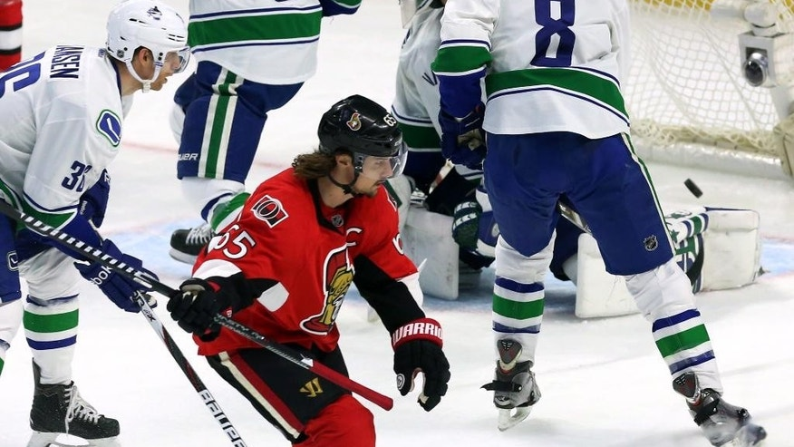 Ottawa Senators' Erik Karlsson (65) reacts after shooting the puck past Vancouver Canucks goalie Eddie Lackduring during overtime in an NHL hockey game in Ottawa, Ontario, Sunday, Dec. 7, 2014. (AP Photo/The Canadian Press, Fred Chartrand)