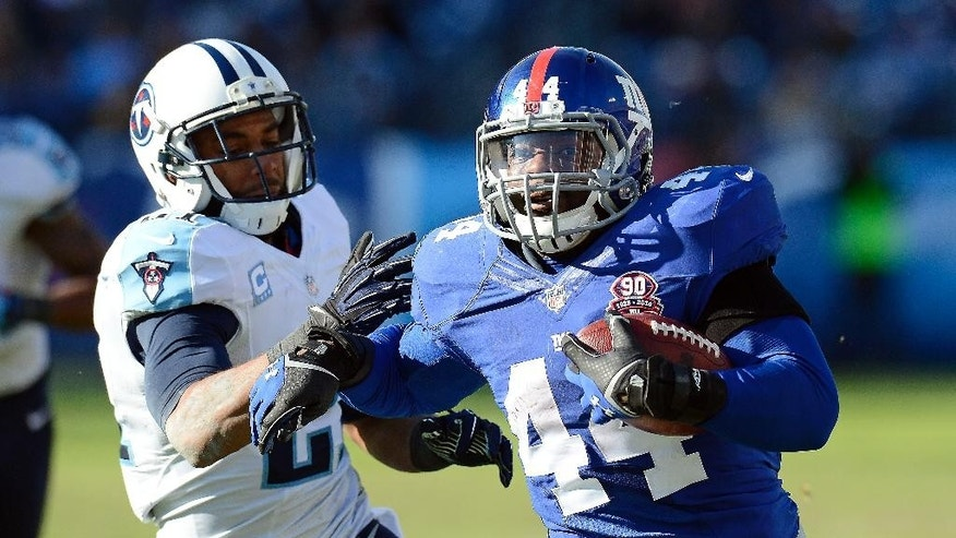 New York Giants running back Andre Williams (44) scores a touchdown against the Tennessee Titans on a 50-yard run in the second half of an NFL football game Sunday, Dec. 7, 2014, in Nashville, Tenn. At left is Tennessee Titans safety George Wilson (21). (AP Photo/Mark Zaleski)