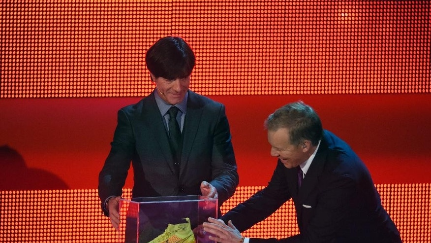 "In this Saturday Dec. 6, 2014 picture , German TV presenter Johannes B Kerner , right, and  German national team's head coach Joachim Loew, left, take a look at the left soccer shoe of Germany's midfielder Mario Goetze  that was  be auctioned  during the charity gala ""Ein Herz fuer Kinder"" (A Heart for Children) a in Berlin. This gala is the German major television fundraising gala .  Mario Goetze's World Cup-winning left shoe has fetched 2 million euros (US $ 2.5 million) at a children's charity gala in Germany and is headed for a museum. (AP Photo/Tobias Schwarz,Pool)"