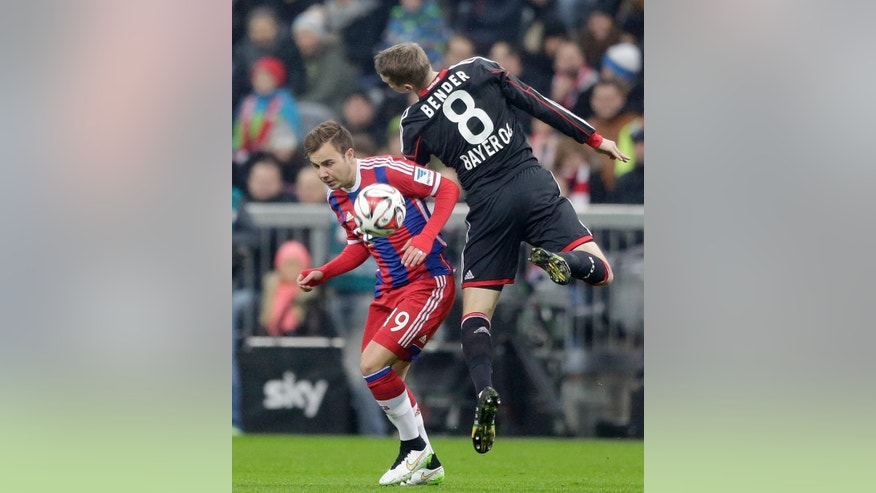 Bayern's Mario Goetze, left, and Leverkusen's Lars Bender challenge for the ball during the German first division Bundesliga soccer match between FC Bayern and Bayer Leverkusen 04 in the Allianz Arena in Munich, Germany, on Saturday, Dec. 6, 2014. (AP Photo/Matthias Schrader)