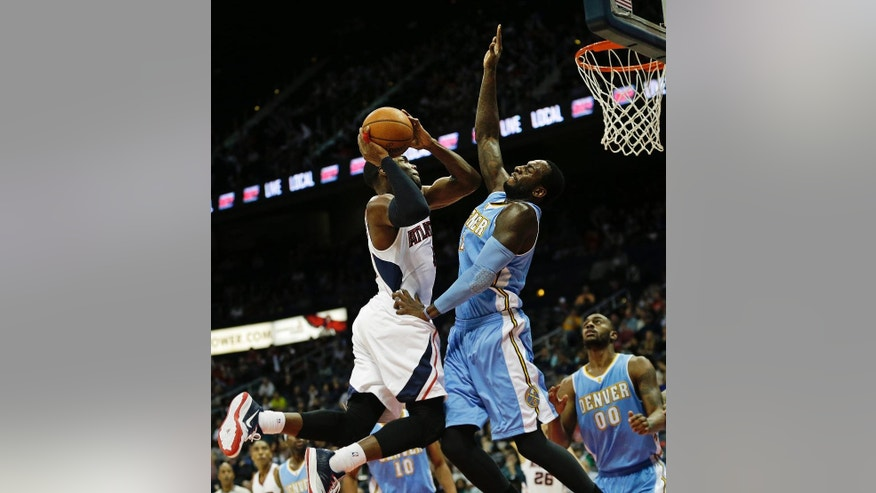 Atlanta Hawks' Paul Millsap, left, goes up to shoot against Denver Nuggets' J.J. Hickson in the first quarter of an NBA basketball game, Sunday, Dec. 7, 2014, in Atlanta. (AP Photo/David Goldman)