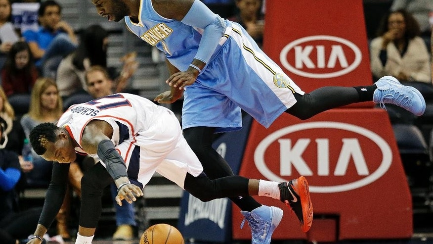 Atlanta Hawks' Dennis Schroder, of Germany, left, chases a loose ball in front of Denver Nuggets' J.J. Hickson in the first quarter of an NBA basketball game, Sunday, Dec. 7, 2014, in Atlanta. (AP Photo/David Goldman)