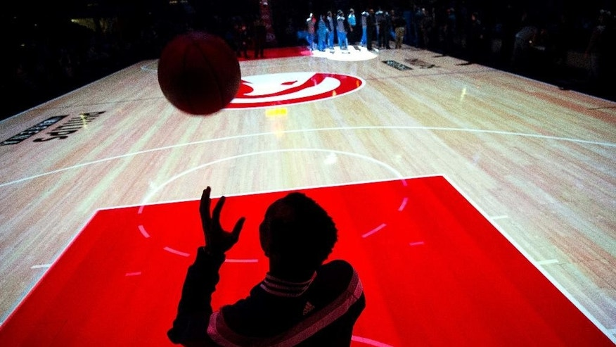 Atlanta Hawks' Dennis Schroder, of Germany, is silhouetted against a backlit court while warming up before an NBA basketball game against the Denver Nuggets, Sunday, Dec. 7, 2014, in Atlanta. (AP Photo/David Goldman)