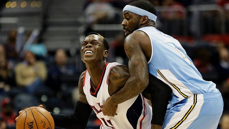 Atlanta Hawks' Dennis Schroder, left, of Germany, dribbles against Denver Nuggets' Ty Lawson in the first quarter of an NBA basketball game, Sunday, Dec. 7, 2014, in Atlanta. (AP Photo/David Goldman)