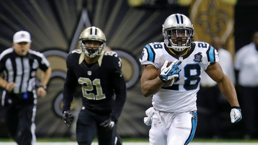 Carolina Panthers running back Jonathan Stewart (28) runs on a 69-yard touchdown carry as New Orleans Saints cornerback Patrick Robinson (21) pursues in the second half of an NFL football game in New Orleans, Sunday, Dec. 7, 2014. (AP Photo/Bill Feig)