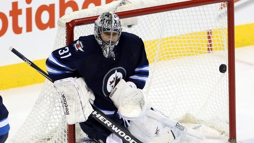 Winnipeg Jets' goaltender Ondrej Pavelec, left, makes a save with Anaheim Ducks Matt Beleskey (39) in front of the net during second-period NHL hockey action in Winnipeg, Manitoba, Sunday, Dec. 7, 2014. (AP Photo/The Canadian Press, Trevor Hagan)
