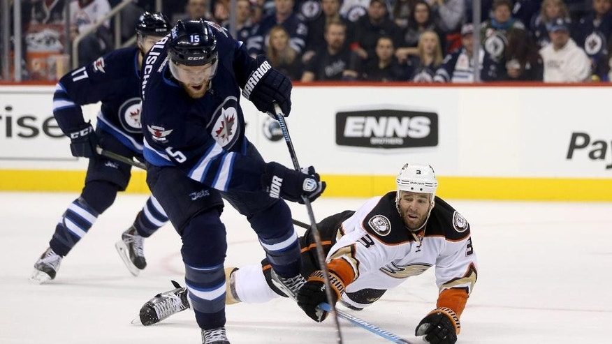 Winnipeg Jets' Matt Halischuk (15) shoots as Anaheim Ducks' Clayton Stoner (3) tries to blockthe shot during second-period NHL hockey action in Winnipeg, Manitoba, Sunday, Dec. 7, 2014. (AP Photo/The Canadian Press, Trevor Hagan)