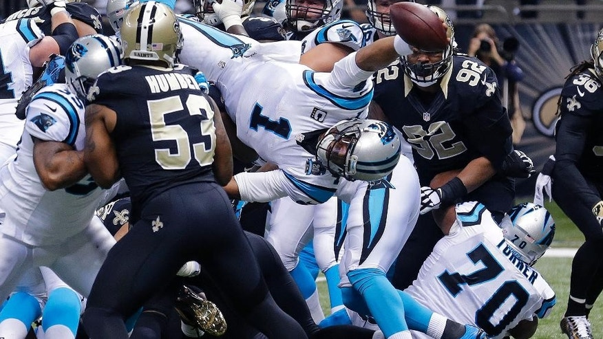 Carolina Panthers quarterback Cam Newton (1) dives over the pile for a touchdown in the first half of an NFL football game against the New Orleans Saints in New Orleans, Sunday, Dec. 7, 2014. (AP Photo/Bill Haber)