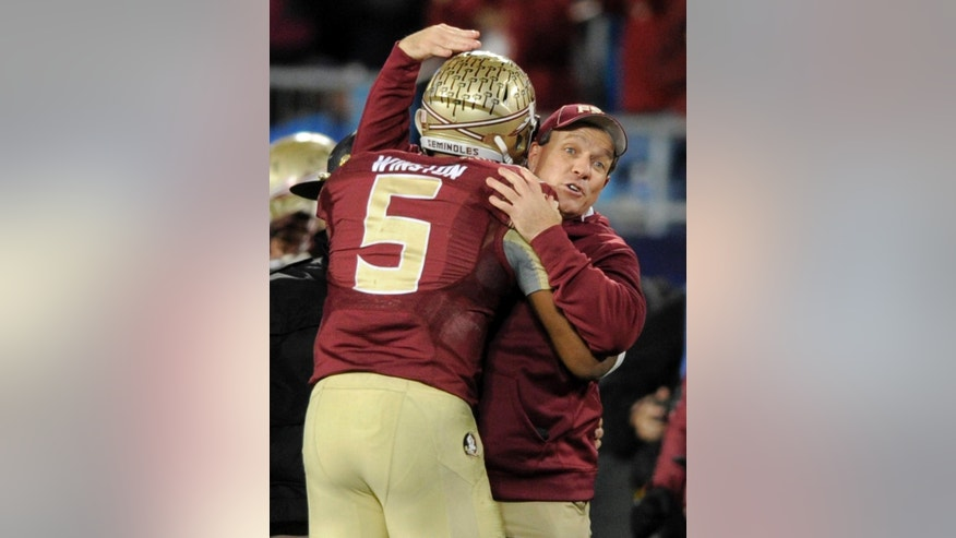 Florida State head coach Jimbo Fisher, right, embraces quarterback Jameis Winston, left, after winning the Atlantic Coast Conference championship NCAA college football game in Charlotte, N.C., Saturday, Dec. 6, 2014. Florida State won 37-35. (AP Photo/Mike McCarn)