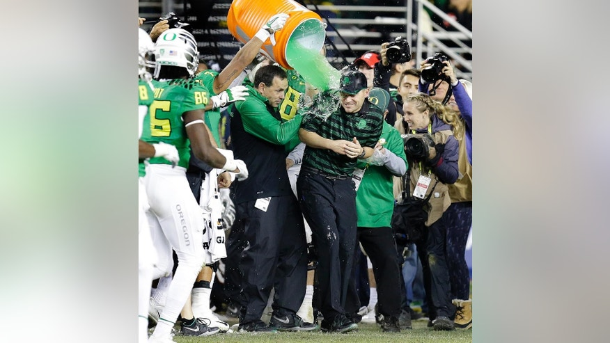 Oregon coach Mark Helfrich is drenched with a green liquid during the second half of a Pac-12 Conference championship against Arizona NCAA college football game Friday, Dec. 5, 2014, in Santa Clara, Calif. Oregon won, 51-13. (AP Photo/Ben Margot)
