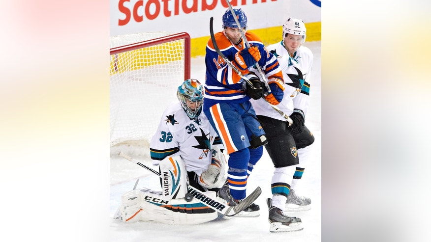 San Jose Sharks goalie Alex Stalock (32) makes the save as he is screened by Edmonton Oilers' Jordan Eberle (14) and Sharks' Justin Braun (61) during second period of an NHL hockey game in Edmonton, Alberta, Sunday, Dec. 7, 2014. (AP Photo/The Canadian Press, Jason Franson)