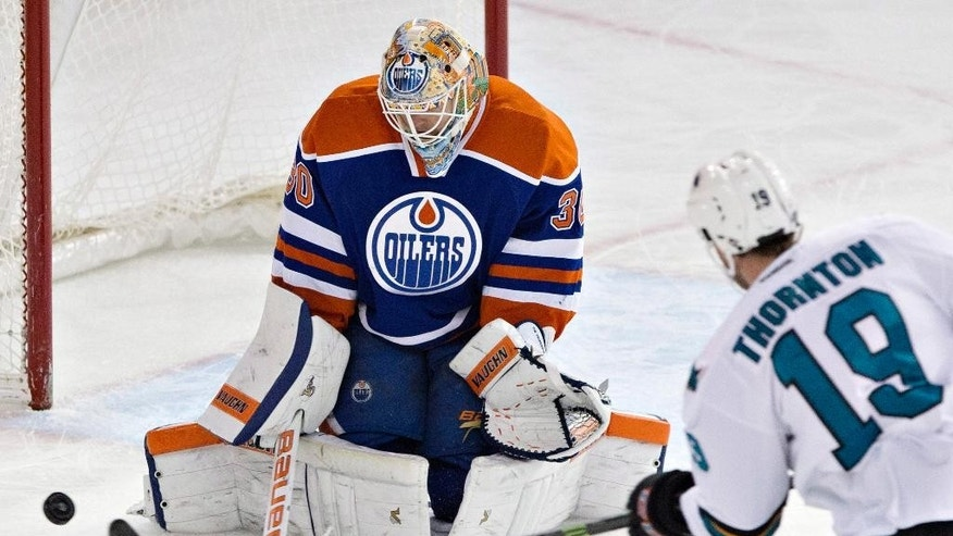 San Jose Sharks' Joe Thornton (19) is stopped by Edmonton Oilers goalie Ben Scrivens (30) during third period of an NHL hockey game in Edmonton, Alberta, Sunday, Dec. 7, 2014. (AP Photo/The Canadian Press, Jason Franson)