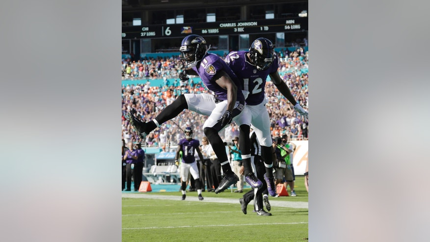 Baltimore Ravens wide receivers Kamar Aiken (11) and Jacoby Jones (12) celebrate after Aiken scored a touchdown during the second half of an NFL football game against the Miami Dolphins, Sunday, Dec. 7, 2014, in Miami Gardens, Fla. (AP Photo/Lynne Sladky)