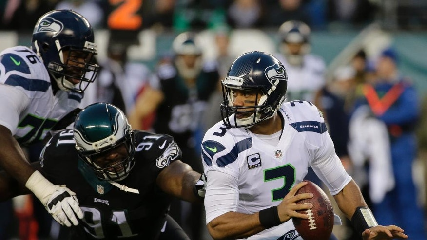Seattle Seahawks' Russell Wilson scrambles away from  Philadelphia Eagles' Fletcher Cox as Russell Okung defends during the first half of an NFL football game against the Philadelphia Eagles, Sunday, Dec. 7, 2014, in Philadelphia. (AP Photo/Michael Perez)