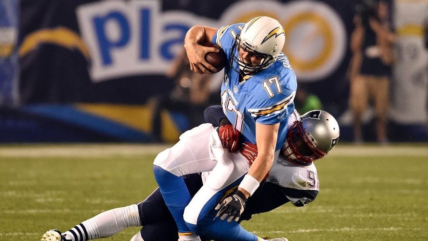 San Diego Chargers quarterback Philip Rivers is brought down by New England Patriots outside linebacker Jamie Collins during the first half in an NFL football game Sunday, Dec. 7, 2014, in San Diego. (AP Photo/Denis Poroy)