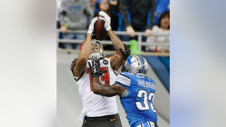Tampa Bay Buccaneers wide receiver Mike Evans (13), defended by Detroit Lions strong safety James Ihedigbo (32), makes a catch for a 26-yard touchdown during the second half of an NFL football game in Detroit, Sunday, Dec. 7, 2014. (AP Photo/Paul Sancya)