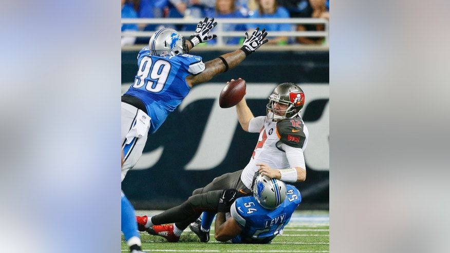 Tampa Bay Buccaneers quarterback Josh McCown is sacked by Detroit Lions outside linebacker DeAndre Levy (54) as Lions defensive tackle C.J. Mosley (99) closes in during the second half of an NFL football game in Detroit, Sunday, Dec. 7, 2014. (AP Photo/Rick Osentoski)