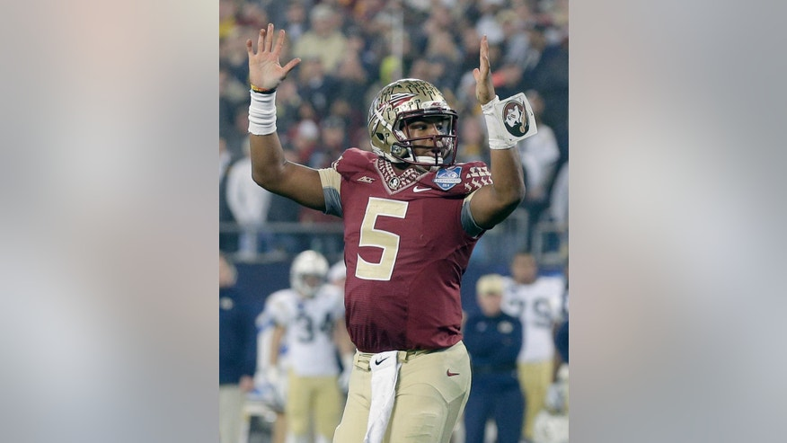 Florida State quarterback Jameis Winston (5) raises his arms after a touchdown against Georgia Tech during the first half of the Atlantic Coast Conference championship NCAA college football game in Charlotte, N.C., Saturday, Dec. 6, 2014. (AP Photo/Chuck Burton)