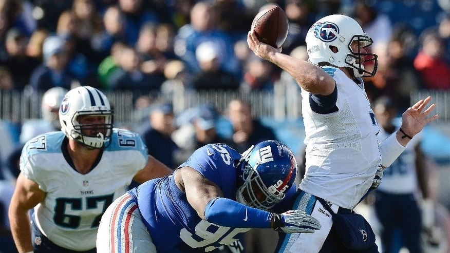 Tennessee Titans quarterback Zach Mettenberger (7) passes as he is hit by New York Giants defensive tackle Johnathan Hankins (95) in the first half of an NFL football game Sunday, Dec. 7, 2014, in Nashville, Tenn. (AP Photo/Mark Zaleski)