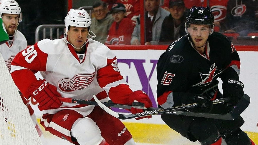 Carolina Hurricanes' Elias Lindholm (16) of Sweden, tries to control the puck on his stick in front of Detroit Red Wings' Stephen Weiss (90) during the second period of an NHL hockey game in Raleigh, N.C., Sunday, Dec. 7, 2014. (AP Photo/Karl B DeBlaker)