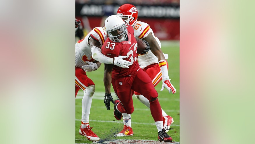 Arizona Cardinals' Kerwynn Williams (33) gets past Kansas City Chiefs' Husain Abdullah, left, and Sean Smith (21) as he runs the ball during the first half of an NFL football game Sunday, Dec. 7, 2014, in Glendale, Ariz.  The Cardinals defeated the Chiefs 17-14. (AP Photo/Ross D. Franklin)