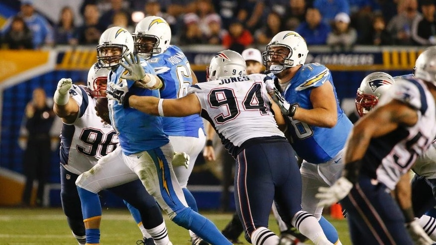 San Diego Chargers quarterback Philip Rivers tries to get away from New England Patriots defensive tackle Chris Jones (94) during the second half in an NFL football game Sunday, Dec. 7, 2014, in San Diego. (AP Photo/Lenny Ignelzi)
